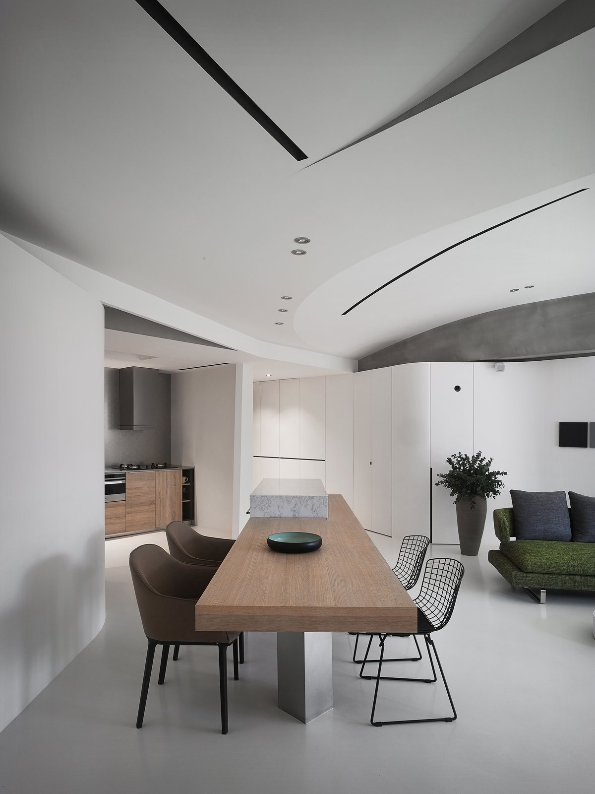 The living space is equipped with a home cinema and a mini bar to enhance the entertainment facilities for social activities.  Tagged: Dining Room, Chair, Ceiling Lighting, Table, Bar, and Concrete Floor.  Fluid House