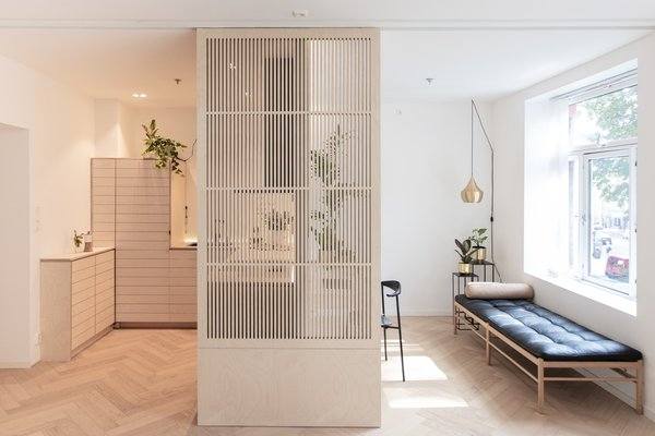 An Oslo apartment by architect Johan Tran features a Nordic and Japanese sensibilities. A Japanese-inspired sliding door made of birch plywood acts as a flexible room divider.