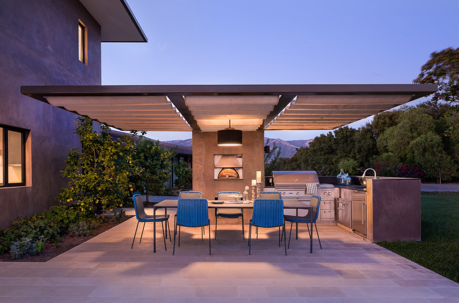 """Outdoor, Back Yard, Hardscapes, Concrete Patio, Porch, Deck, and Grass """"Designed to take advantage of expansive ocean, island, and mountain views, this contemporary remodel and addition recycled the original 1948 ranch house to create a new two-story home with an open plan layout,"""" says Blackbird Architects. The outdoor hardscape and garden include a reflection koi pond and palm island at the entry, green roofs, an outdoor kitchen, a pizza oven, and a fire pit.  Hope Ranch Residence by Blackbird Architects"""