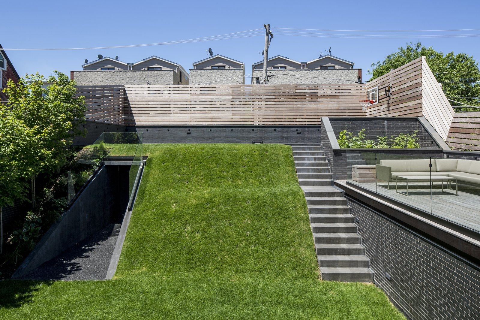 """Outdoor, Grass, Trees, Back Yard, Horizontal Fences, Wall, Wood Patio, Porch, Deck, Wood Fences, Wall, and Slope Play surface and """"hill"""" covers garage  Mohawk House by UrbanLab"""