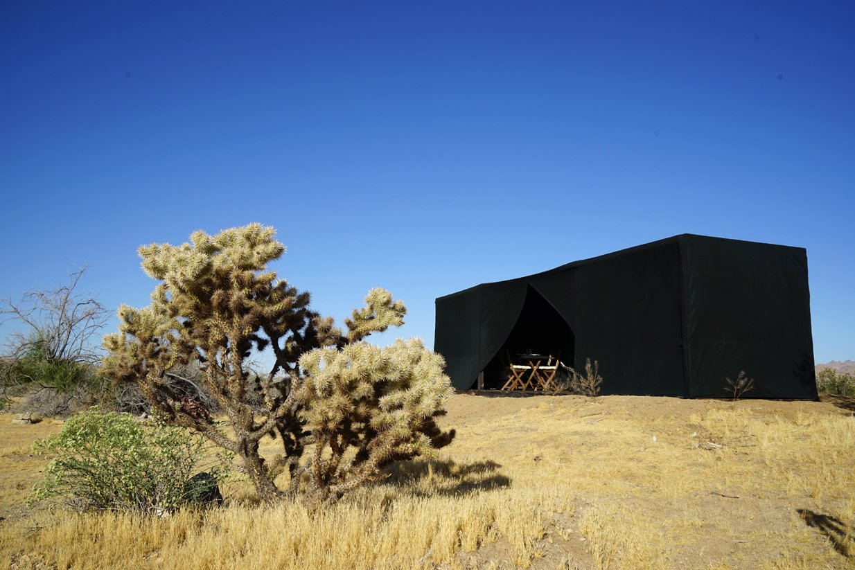 Cabin shown with fabric shell and cholla cactus in the foreground  Joshua Tree Case Study Cabin by Mike Vensel