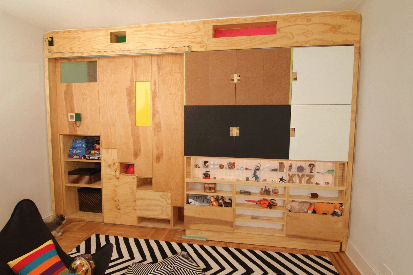 Kids Room, Playroom Room Type, Chair, Bookcase, Shelves, Storage, Boy Gender, Pre-Teen Age, Medium Hardwood Floor, and Neutral Gender Step-storage and moving divider panel as seen from playroom with storage and usable surfaces  LO Residence Playroom/Bedroom