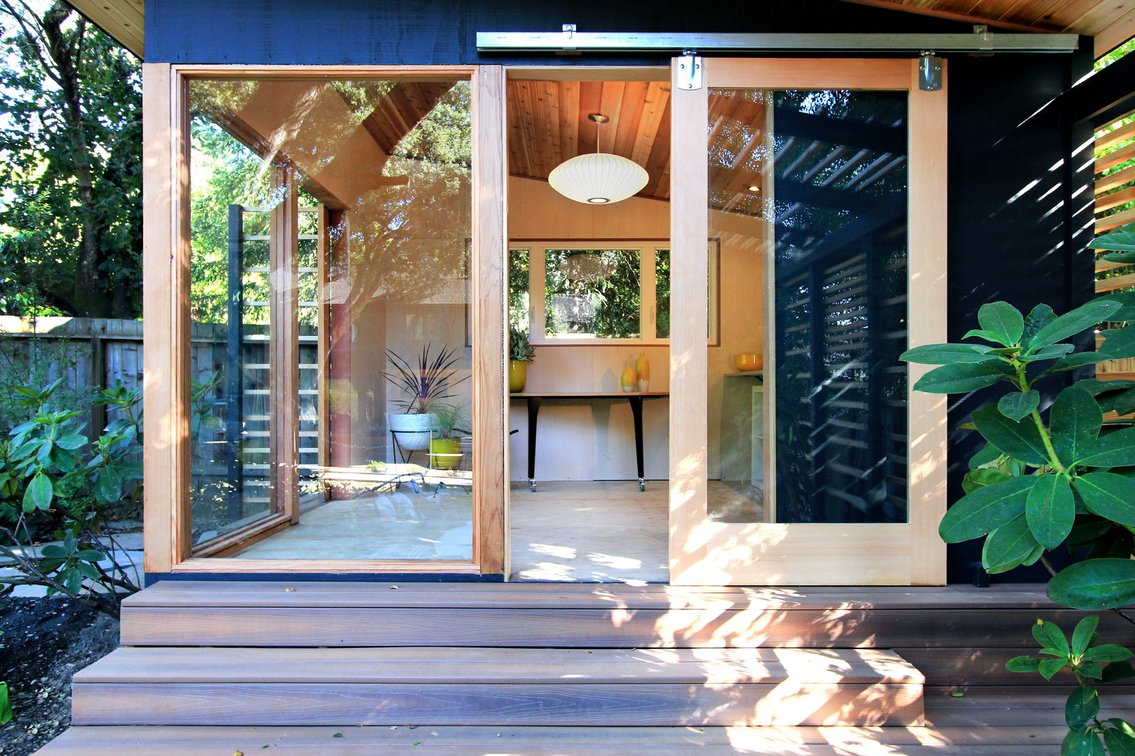 Boulders, Wood Patio, Porch, Deck, Hanging Lighting, Landscape Lighting, Horizontal Fences, Wall, and Kids Room The Shudio exterior and interior.   The Shudio by Melissa Hanley
