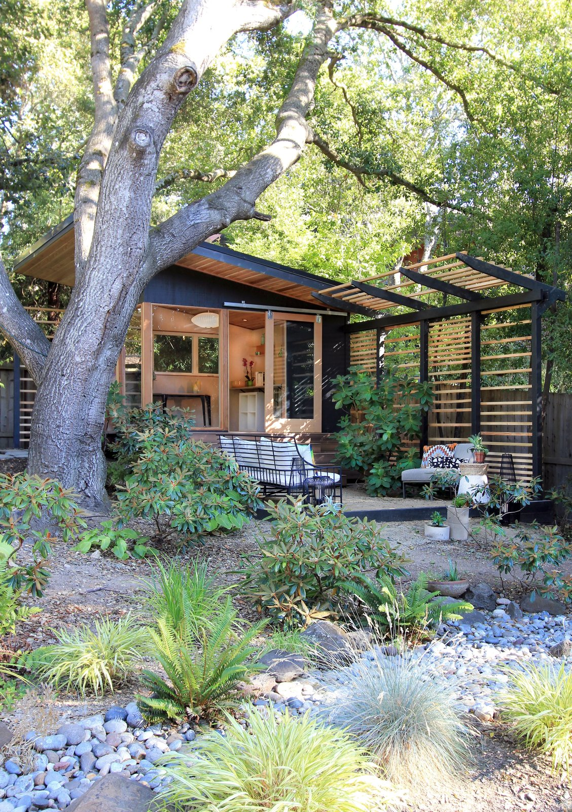 Outdoor, Back Yard, Garden, Woodland, Trees, Flowers, Shrubs, Boulders, Small Patio, Porch, Deck, Walkways, Decomposed Granite Patio, Porch, Deck, Pavers Patio, Porch, Deck, Gardens, Landscape Lighting, Decking Patio, Porch, Deck, Horizontal Fences, Wall, and Hanging Lighting The Shudio and patio with dry river bed in foreground  The Shudio by Melissa Hanley