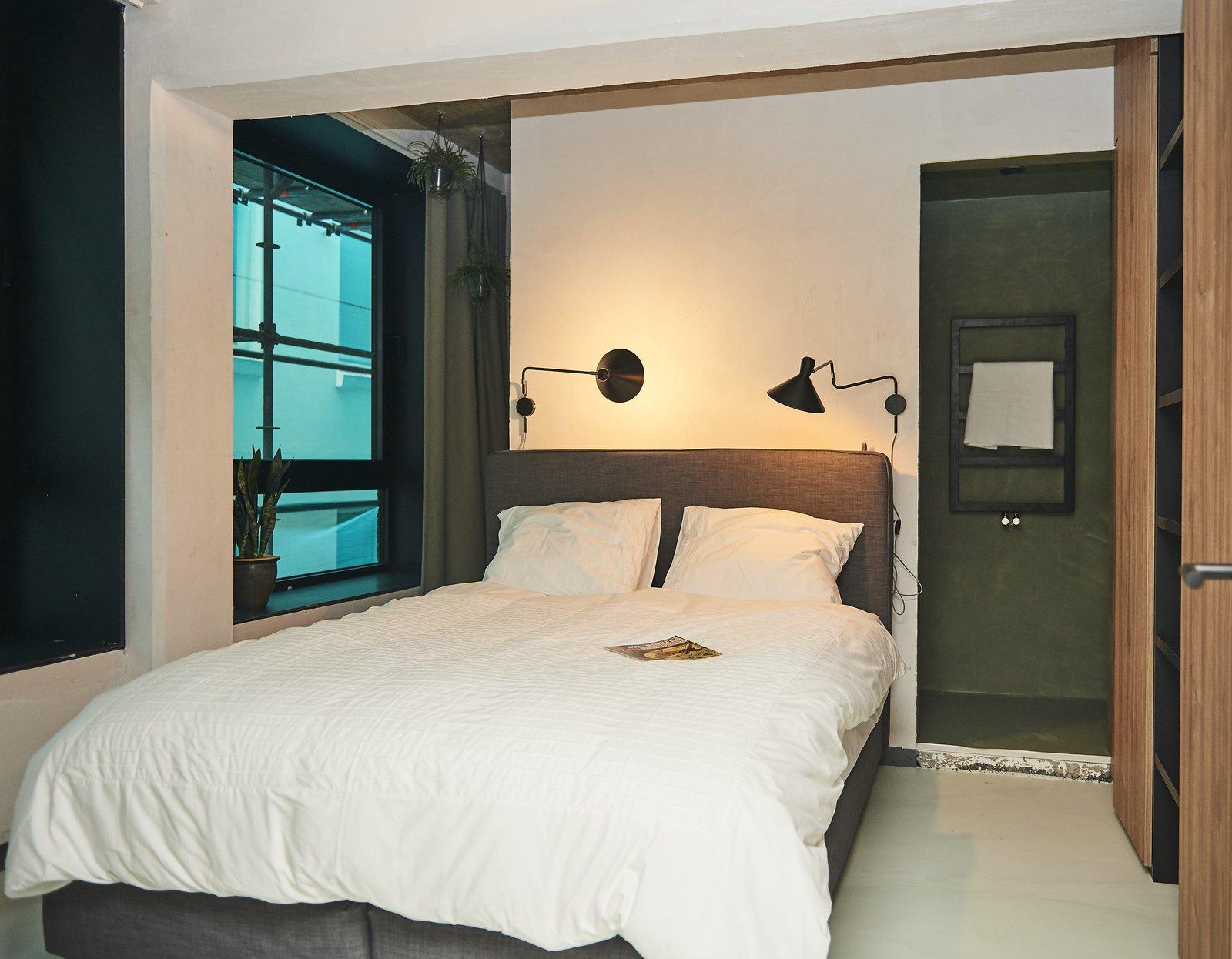Bed, Wardrobe, Storage, Floor Lighting, Ceiling Lighting, Wall Lighting, Lamps, Living Room, and Concrete Floor Bedroom  HUT