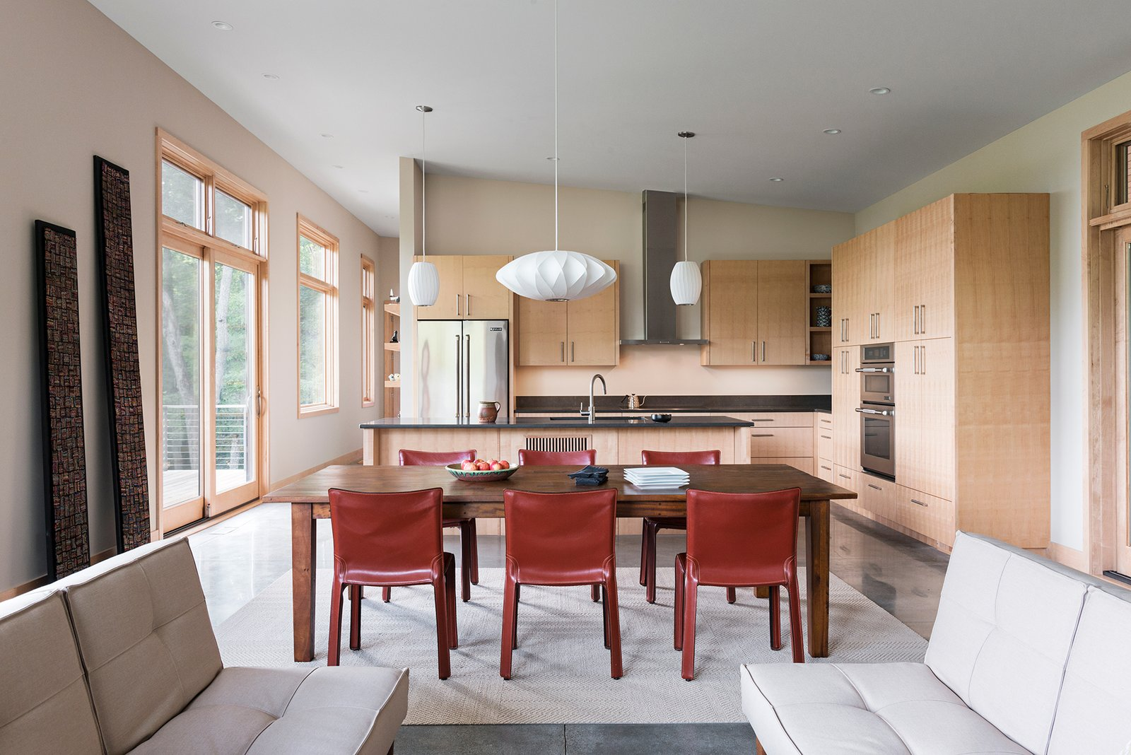 Kitchen, Concrete Floor, Wood Cabinet, Pendant Lighting, Refrigerator, Wall Oven, Range Hood, Range, and Undermount Sink The main living spaces are arranged in a light-filled open floor plan.  Craven Gap Residence by Samsel Architects