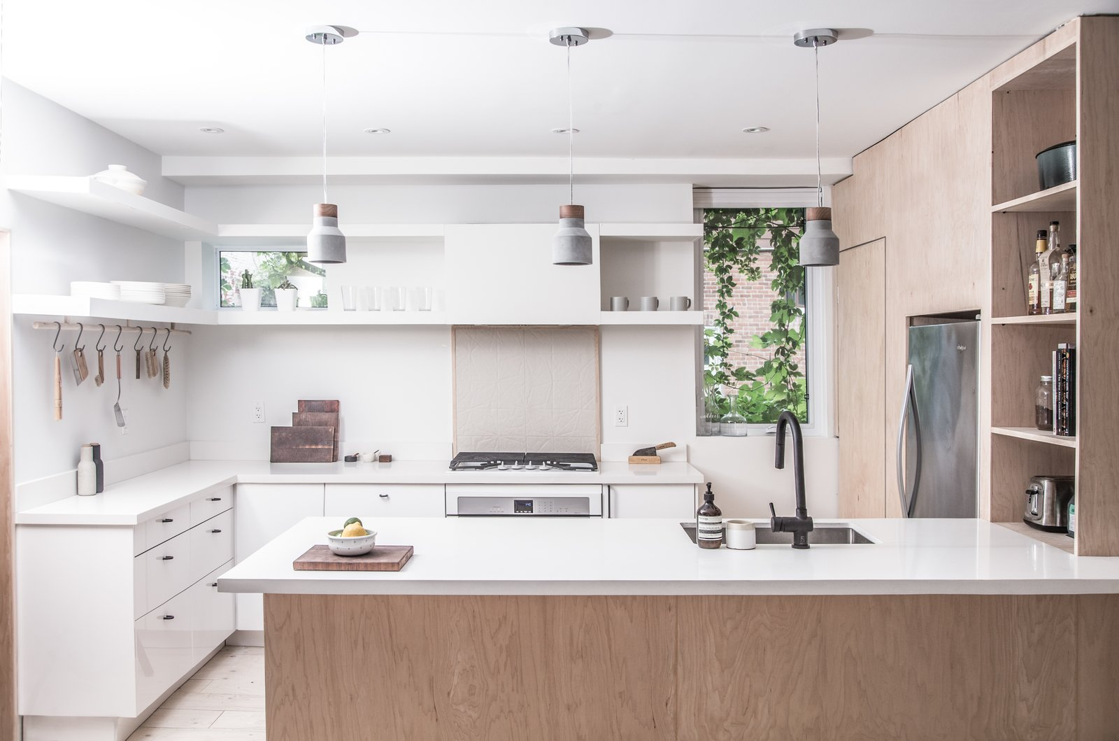 """Kitchen, Refrigerator, Range, Pendant Lighting, Recessed Lighting, Open Cabinet, Wall Oven, Undermount Sink, and Light Hardwood Floor <span style=""""font-family: Theinhardt, -apple-system, BlinkMacSystemFont, &quot;Segoe UI&quot;, Roboto, Oxygen-Sans, Ubuntu, Cantarell, &quot;Helvetica Neue&quot;, sans-serif;"""">For this small west Toronto renovation, rather than imagine a home comprised of rooms within an open plan the architects conceived a room revolving around a singular mass.</span>  Sheridan Residence"""