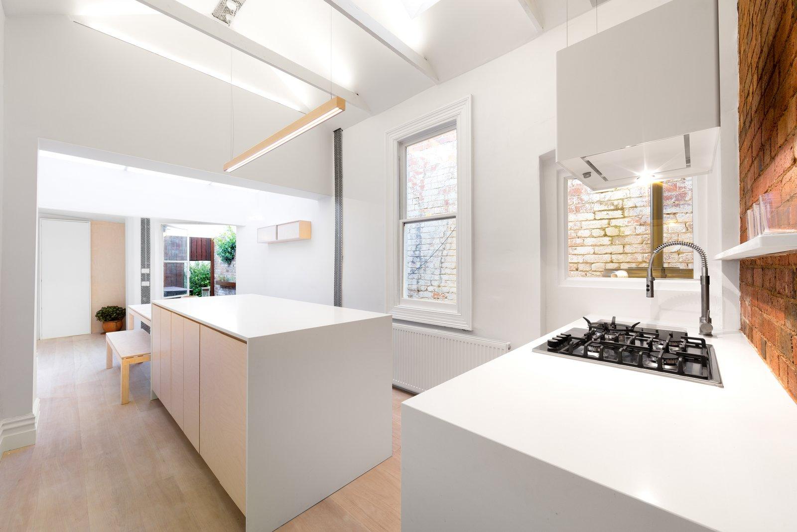 Kitchen, Engineered Quartz Counter, Wood Cabinet, Light Hardwood Floor, Ceiling Lighting, Brick Backsplashe, Pendant Lighting, Recessed Lighting, Accent Lighting, Cooktops, Range, and Range Hood Kitchen  Curtain Cottage