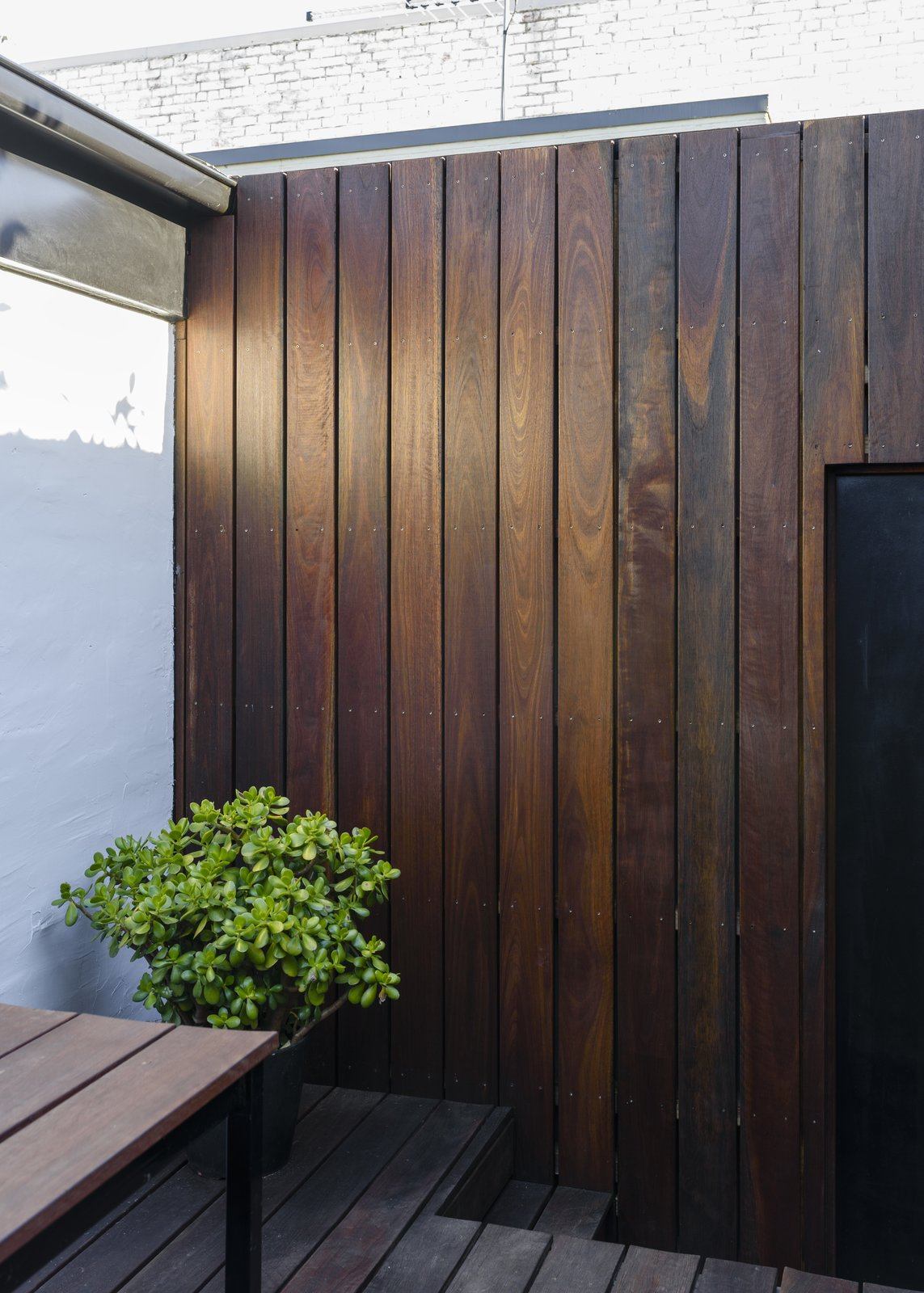 Outdoor, Back Yard, Shrubs, Small Patio, Porch, Deck, Hardscapes, Gardens, Decking Patio, Porch, Deck, Planters Patio, Porch, Deck, Wood Fences, Wall, and Wood Patio, Porch, Deck Courtyard wall detail  Curtain Cottage
