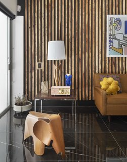 """Florentino hired a local woodworker to create wood-paneled slated walls out of Angelique wood, mimicking a type of decor common in midcentury homes. The elephant stool is a cherrywood Eames: """"It's one of my favorite things."""""""