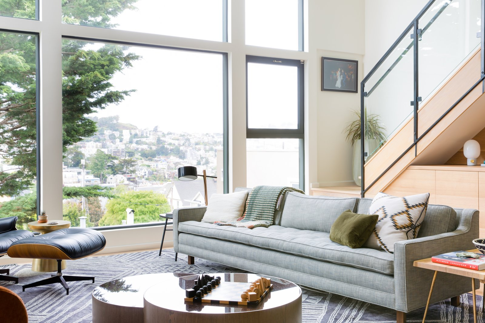 This oversized Artless Up Three Seater is paired with an Eames Lounge Chair and a grey oak frame Berkeley Nesting Coffee Table, encapsulated by a large Geo Megali rug from Anthropologie.  Photo 4 of 5 in How Much Should You Spend on a Living Room Sofa?