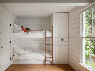 """Bunk beds served Jessica's two young children for four years in the tiny home. They each had a small niche in the wall, illuminated by a pull chain light, where they could store a few things, and a pull out closet at the end of the beds for clothing.  A day bed against the far wall (not pictured) served as the """"guest room."""""""