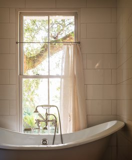 Many of the home's furnishings are made from recycled materials, vintage finds, or nearly new pieces—such as this bathtub, which Jessica salvaged from a renovation at a friend's house. The curtain was made from a vintage French sheet, which ironically—for a bathroom—has the initials BM embroidered on it.