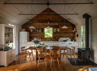 The home's walls are clad in Oregon white oak reclaimed from a dismantled barn on the property. Jessica Helgerson chose to paint them white to create a bright, airy look, but she left the kitchen wall au naturel for a visual pop. With storage at a premium, the kitchen needed ample cabinetry as well as some ingenious solutions—including a pull-out cabinet hidden in one half of the range hood. A vintage cabinet on the left wall provides open storage for everyday dishes.