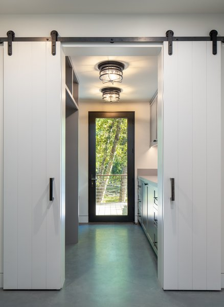 For this mudroom, designer Sarah Latham mixed a black, stainless-steel finish on the exterior with a white bronze dark finish inside.