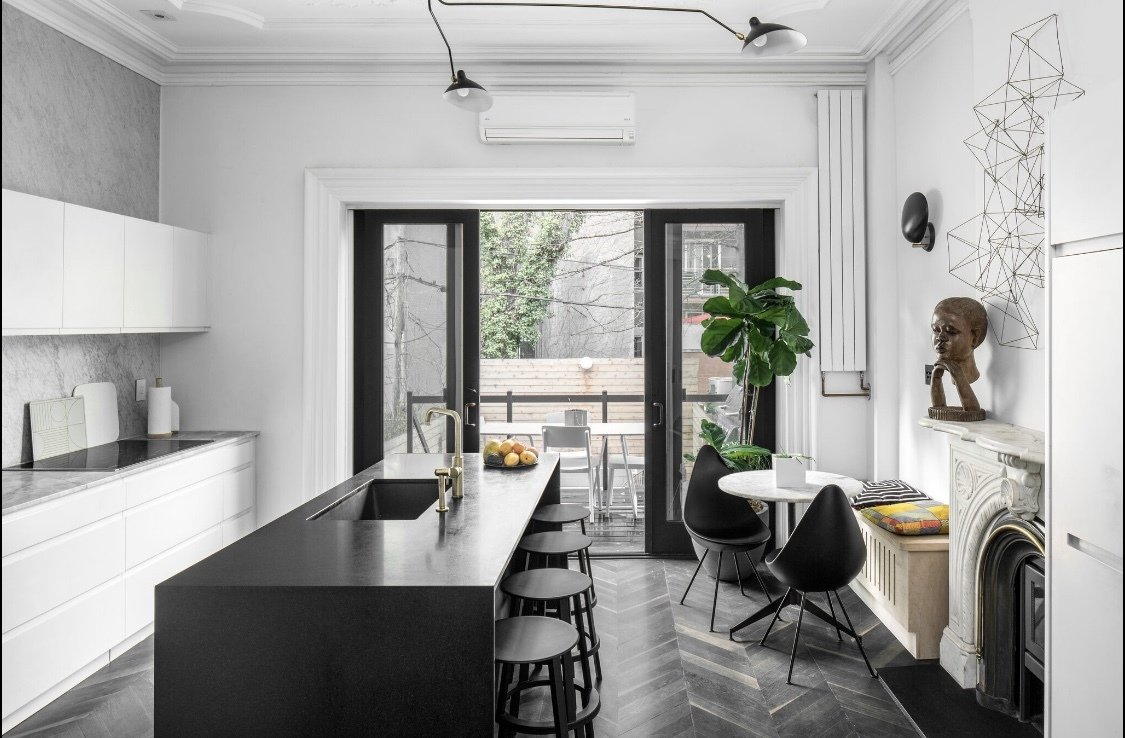 A high-end, natural brass faucet adds a splash of sophistication to this Brooklyn townhouse renovation. Designer Delia Kenza chose the finish as something that would age well while lending a modern touch due to its shape.   Photo 3 of 11 in How Much Should You Spend on a Kitchen Faucet?