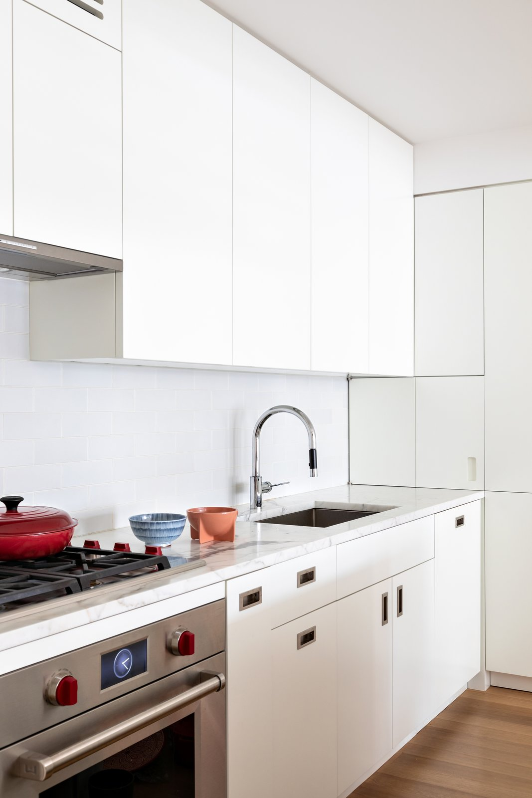 For this apartment overlooking New York City's High Line, the client wanted a clean and minimal aesthetic. Pulltab Design chose Dornbracht's Tara Ultra to make a statement against Chalk White Heath ceramics backsplash and Statuary countertops.   Photo 4 of 11 in How Much Should You Spend on a Kitchen Faucet?