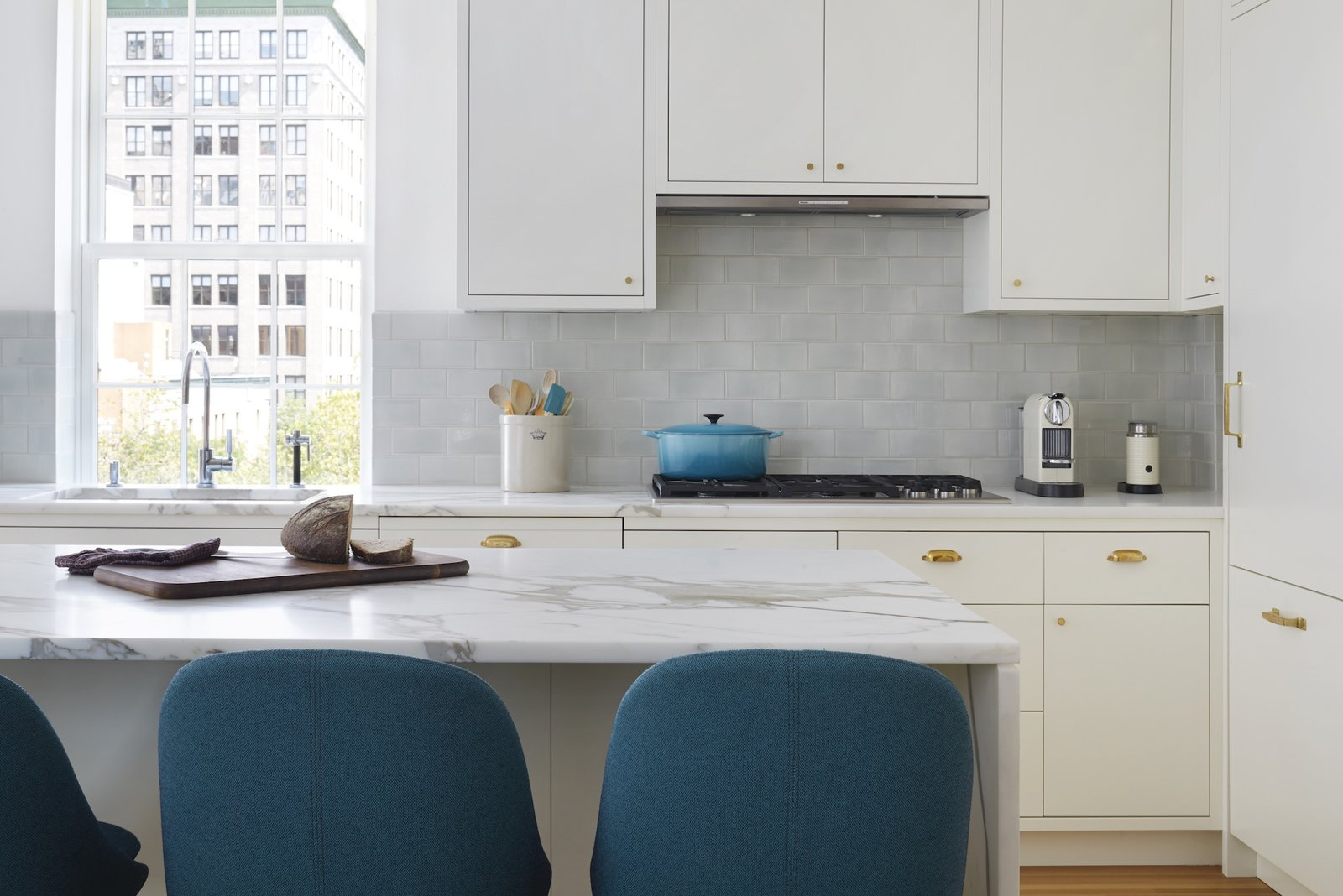 A Dornbracht Tara Classic faucet with separate spray and dispenser competes with the view out to Lower 5th Avenue in this gut renovation by Pulltab Design.  Photo 8 of 11 in How Much Should You Spend on a Kitchen Faucet?