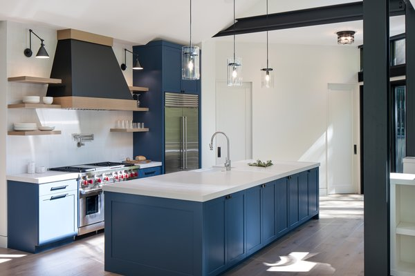 White quartz for the island and countertops offsets dramatic blue cabinetry in the kitchen of this modern home in Sun Valley, Idaho, designed by Sarah Latham.