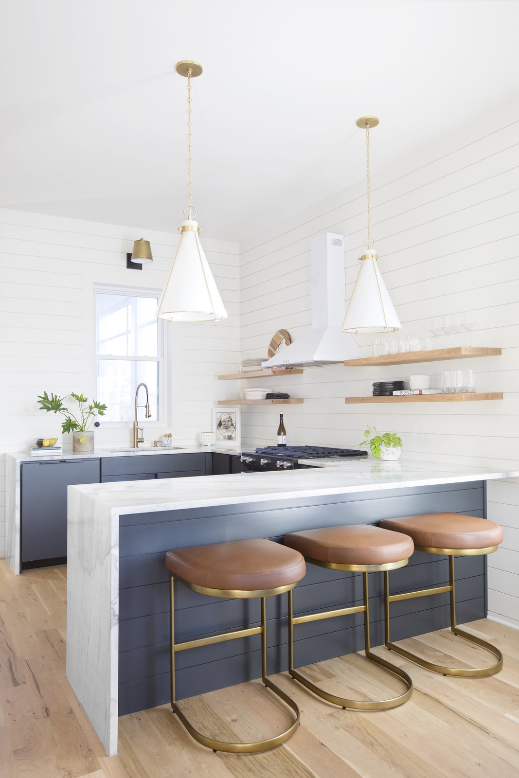 Kitchen, Marble Counter, Ceramic Tile Backsplashe, Undermount Sink, Medium Hardwood Floor, Pendant Lighting, and Colorful Cabinet Designer Jesse Vickers used Rio Venato quartz in her own home in Charleston, South Carolina.  Photo 3 of 13 in How Much Should You Spend on Kitchen Countertops?