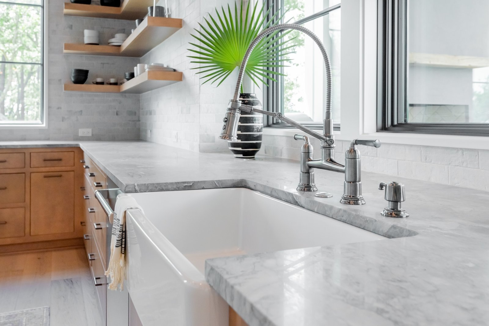 Kitchen, Medium Hardwood Floor, Undermount Sink, Wood Cabinet, Stone Tile Backsplashe, and Marble Counter A gray marble counter adds texture and visual interest to this kitchen designed by Jesse Vickers.   Photo 5 of 13 in How Much Should You Spend on Kitchen Countertops?