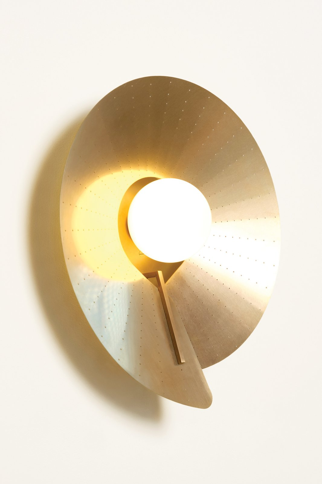Atelier de Troupe's COMPAS sconce ($2,200) is shaped out of a single sheet of brass fastened to a simple spine. Nestled inside is a pearl of hand-blown, sandblasted glass.  Photo 12 of 12 in How Much Should You Spend on a Wall Sconce?