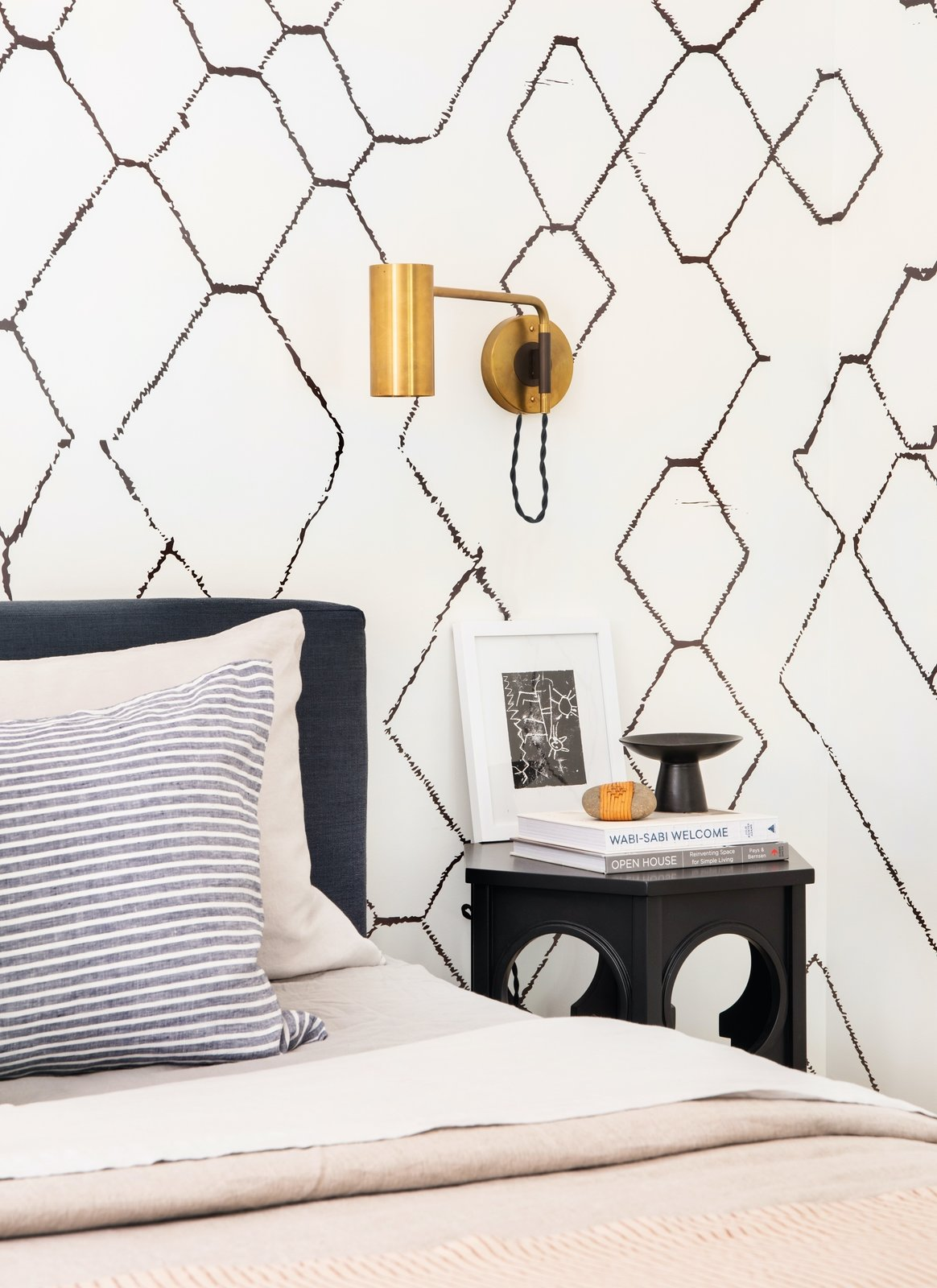 A Schoolhouse Electric brass sconce contrasts with a monochromatic, patterned palette in this bedroom designed by Ginny Macdonald.  Photo 4 of 12 in How Much Should You Spend on a Wall Sconce?