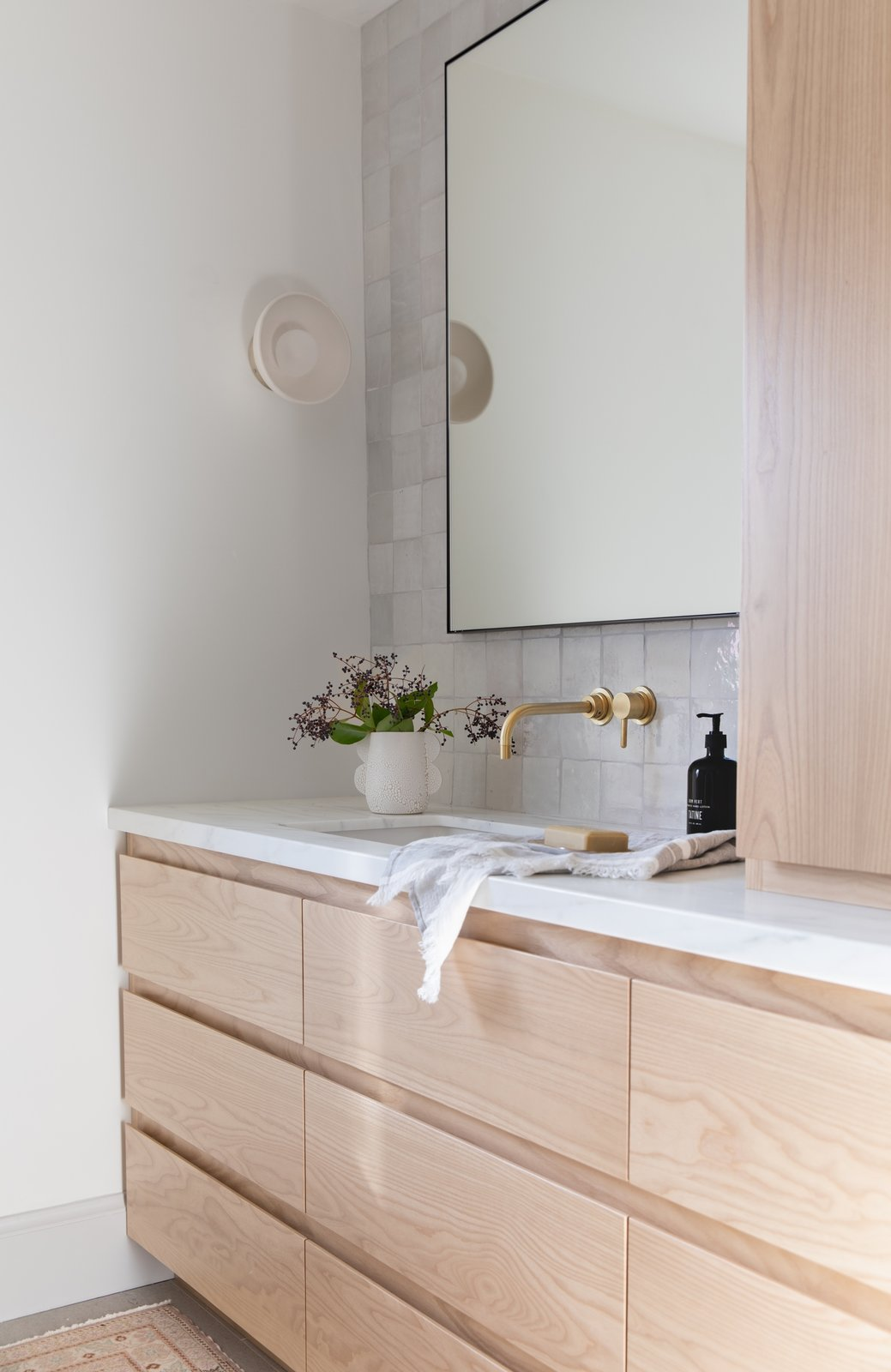 """Wall sconces work well in bathrooms, as the light is closer to your face. """"Overhead lighting can create shadows and uneven illumination, whereas wall sconces can project light outward instead of downward, and close to eye level,"""" says Lauren Nelson, who designed this Los Gatos master bathroom.   Photo 6 of 12 in How Much Should You Spend on a Wall Sconce?"""