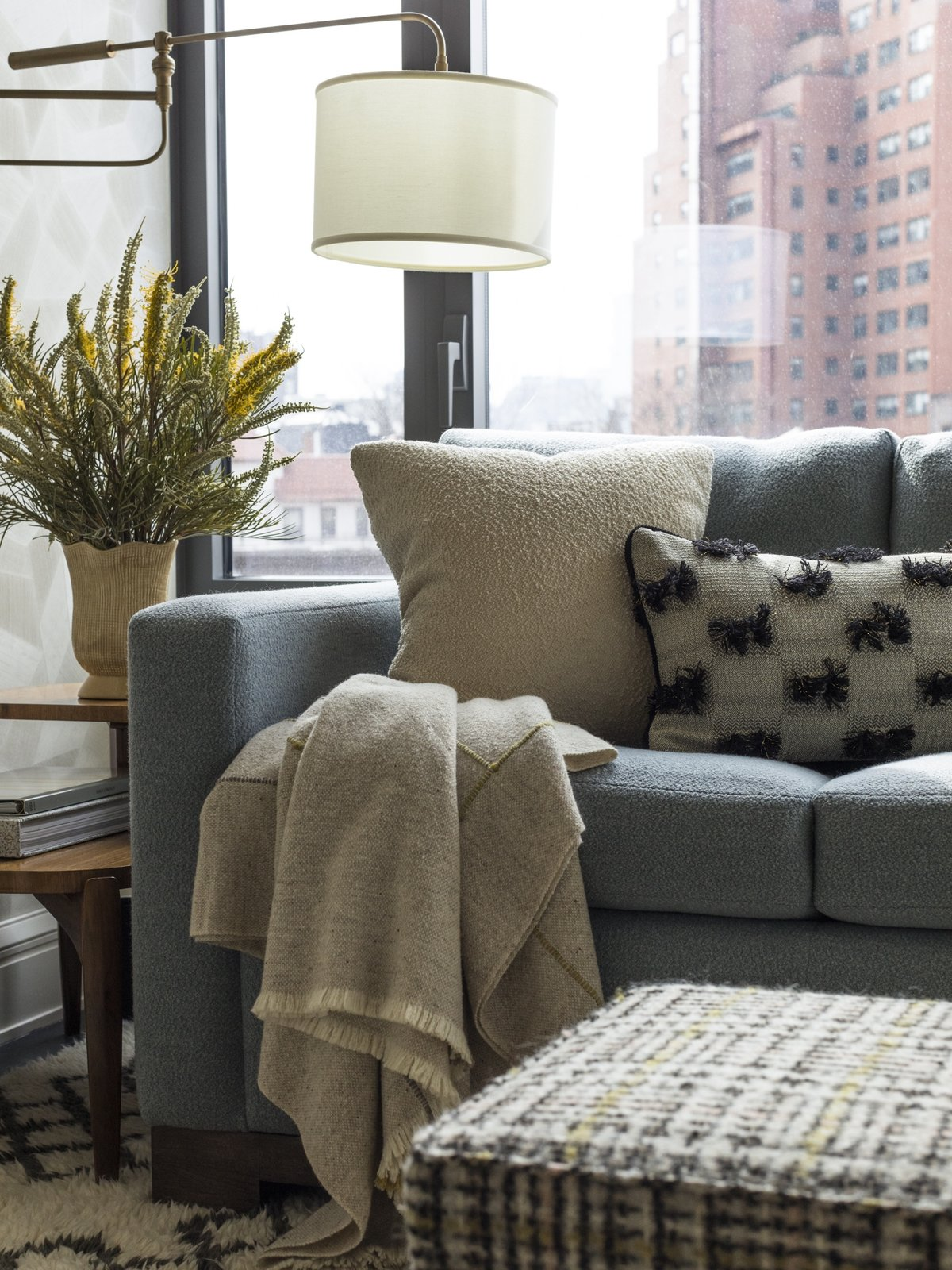 Living Room, Sofa, Rug Floor, Ottomans, Accent Lighting, and Lamps For this family room, Gideon Mendelson chose a high pile, Morrocan-style rug from West Elm that cost $800. The combination of high pile, pattern, and durability means that stains and spills won't be as easily seen.  Photo 6 of 8 in How Much Should You Spend on an Area Rug?