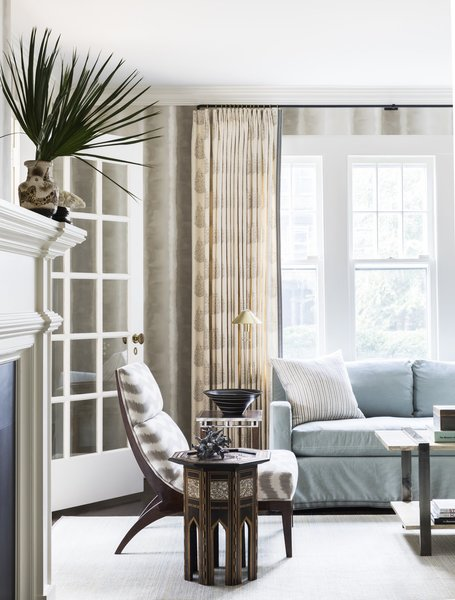 Kevin Isbell selected pinch-pleated, block-print linen curtains with tape trim on the leading and bottom edges, hung from blackened metal rods and brass rings for this calm, clean living room.
