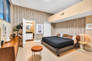 In the bedroom, a king-sized Japanese teak bed with a Saarinen Side Table topped by a Paul McCobb brass lamp are easy bedfellows. Jeff Koons's Hoover Vacuum and an original Keith Haring drawing adorn the space.
