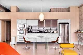 With a '60 space-age feel, the small kitchen is made larger by an elongated, postmodern glass table, complete with Eames fiberglass chairs upholstered in Alexander Girard fabric. The brown fabric of the chairs plays off the walnut teak vinyl cupboards, and black 1940s vintage cabinet pulls provide a soft complement to the shiny, black subway tile backsplash.