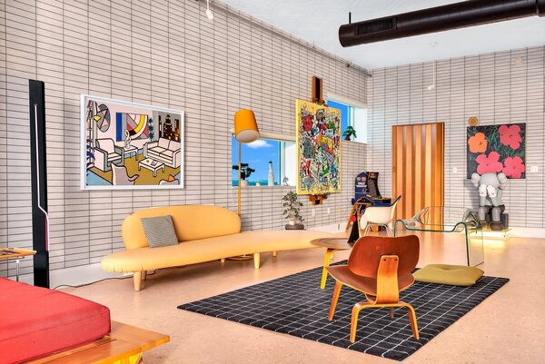 This sitting room–cum–art studio mixes modern with vintage. Flore's prized 1950s Freeform Sofa by Isamu Noguchi, the glass FIAM Ghost Chair by Cini Boeri, and an Eames Plywood Lounge Chair provide plenty of iconic perches from which to contemplate his work—in this case, it's Urban Cubism on the easel.