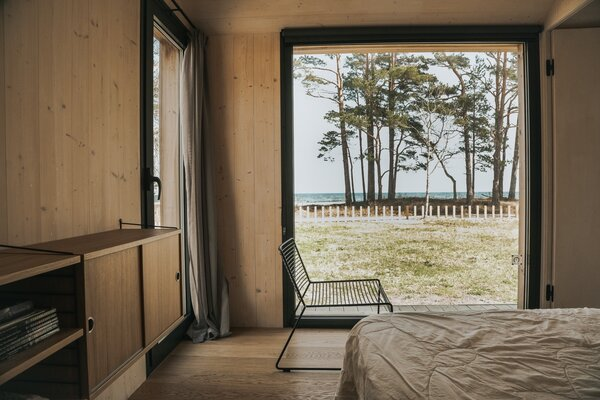 A String Furniture dresser, simple bed, and Hey indoor/outdoor chair complete Laura and Juris' bedroom, whose focal point is the picture window and breathtaking view of the Bay of  Riga.