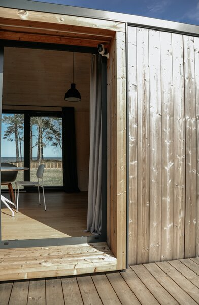 Sliding glass doors help this tiny home expand into an indoor/outdoor living space, augmented by the addition of a deck.