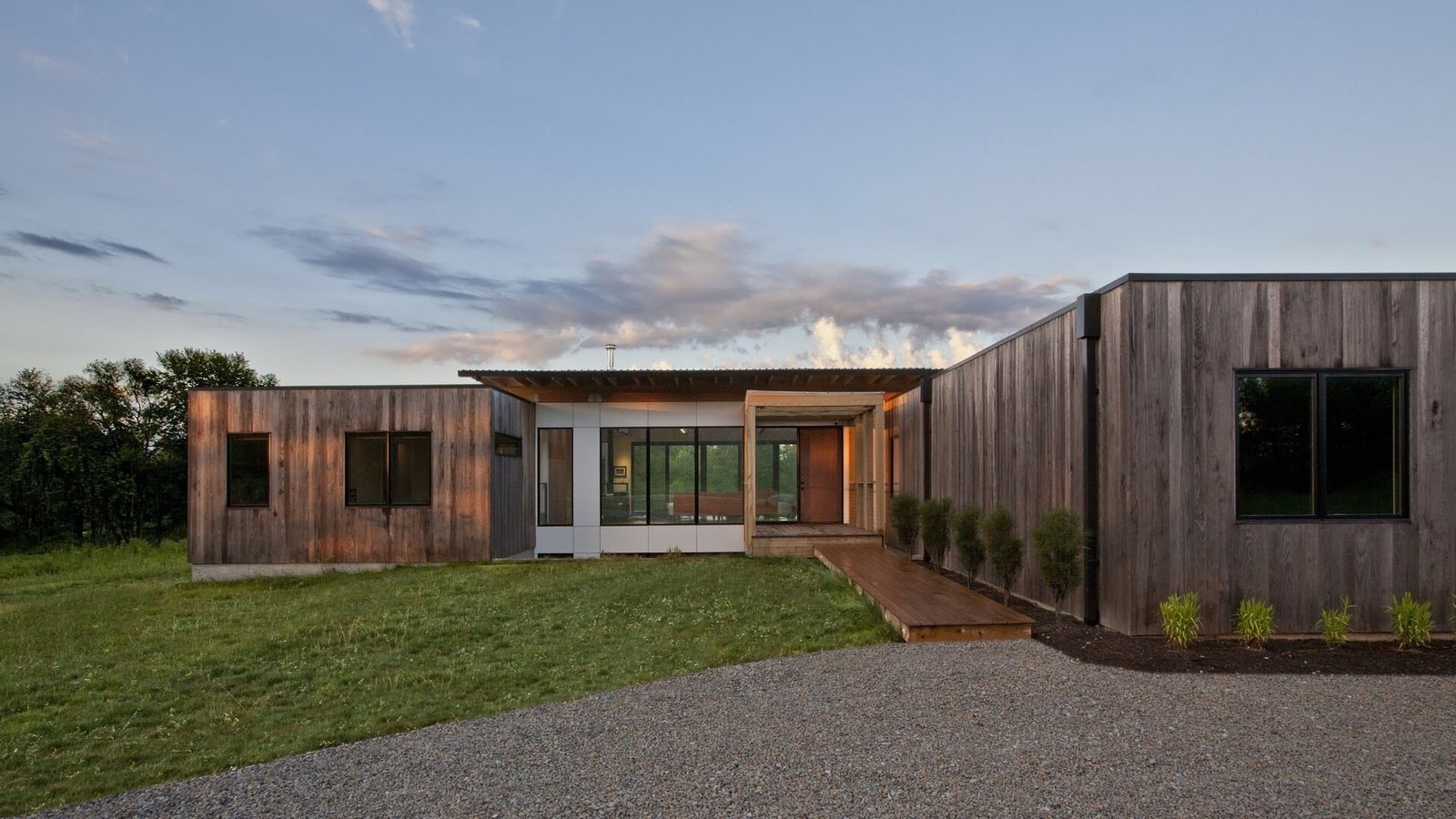 Outdoor, Grass, Field, Shrubs, Front Yard, Hardscapes, Trees, Decking Patio, Porch, Deck, and Large Patio, Porch, Deck Sunrise at Copperwood. The exterior is comprised of thermally treated Ash and white, cement panels.   Copperwood by Kevin Swan