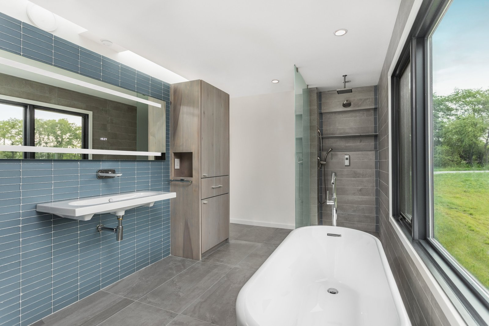 Bath Room, Freestanding Tub, Ceramic Tile Floor, Slate Floor, Wall Mount Sink, Glass Tile Wall, Open Shower, and Ceiling Lighting The modern bathroom with an open shower and simple tile.   Copperwood by Kevin Swan