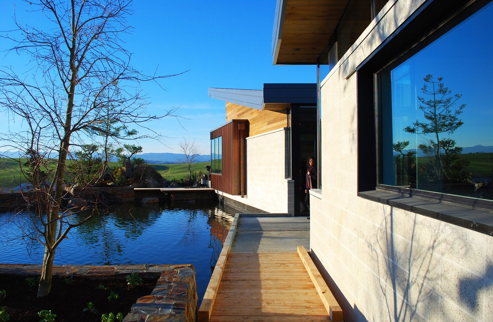 Outdoor, Walkways, Grass, Planters, Field, and Decking The building opens outward to Oregon's quaint wine country.  Best Outdoor Walkways Planters Photos from Saffron Fields Winery