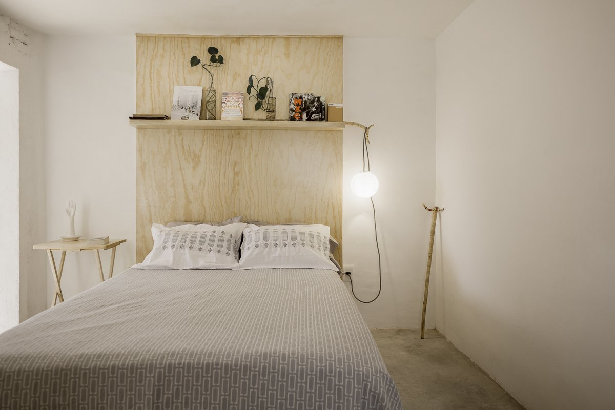 Bedroom, Bed, Shelves, Bookcase, Pendant Lighting, and Concrete Floor Bedroom  Narvarte Terrace