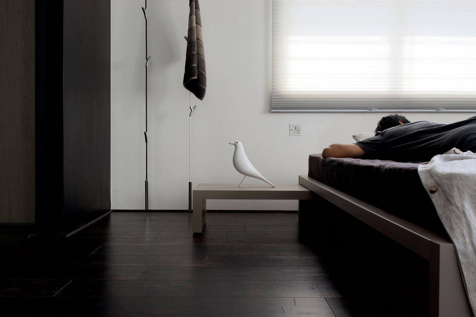 """Bedroom, Dark Hardwood Floor, and Bed """"I studied Product Design at National Institute of Design in India, which is often regarded as Eames school, founded by the designer couple Charles & Ray Eames. The space I wanted to live in wouldn't have been complete without a few of Eames' classics. Quite contrary to where one usually showcase the Eames bird on their shelves, it sits along my bedside waking me up to inspiring mornings every day"""".  Living in Monochrome, far away from Nordic lands by Nithin Ismail"""