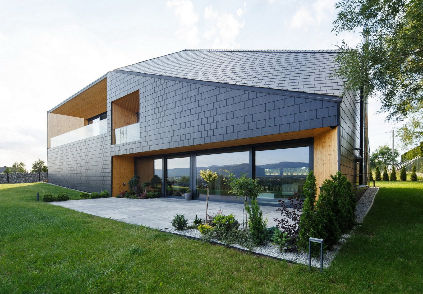 Exterior, Tile Roof Material, Cabin Building Type, House Building Type, Gable RoofLine, Hipped RoofLine, Wood Siding Material, Stone Siding Material, and Shingles Roof Material The southern wall is high and includes openings such as glazing, terrace and loggia, which provide the panoramic view.  BLACK ROCK by MUS ARCHITECTS