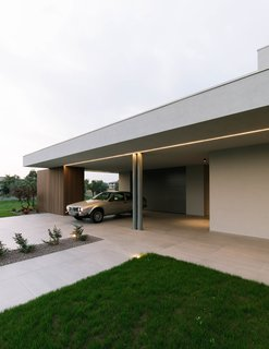 The overhang of House BN provides shelter for the homeowner's automobile. The contemporary villa's entrance corridor faces toward the nearby Monte Grappa mountain.