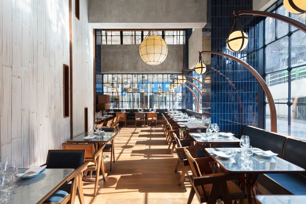 The design is inspired by the crafts of fishing and boating. In fact, the bar's bottle display acts as a nod to lobster cages, while the lanterns draw inspiration from old-school, hand-blown fish floaters. The cobalt color found throughout the space takes cues from the Mediterranean Sea's deep blue hue, and the banquettes are a riff on the Star Ferry's seating as they flip from one side to the other.
