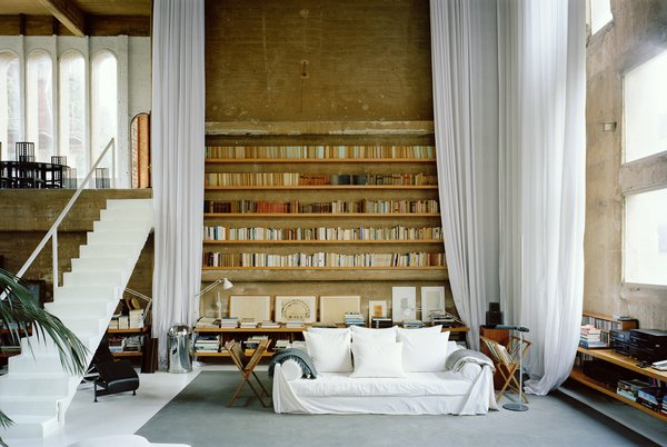 In the living room, ethereal white curtains soften the severity of the concrete walls.