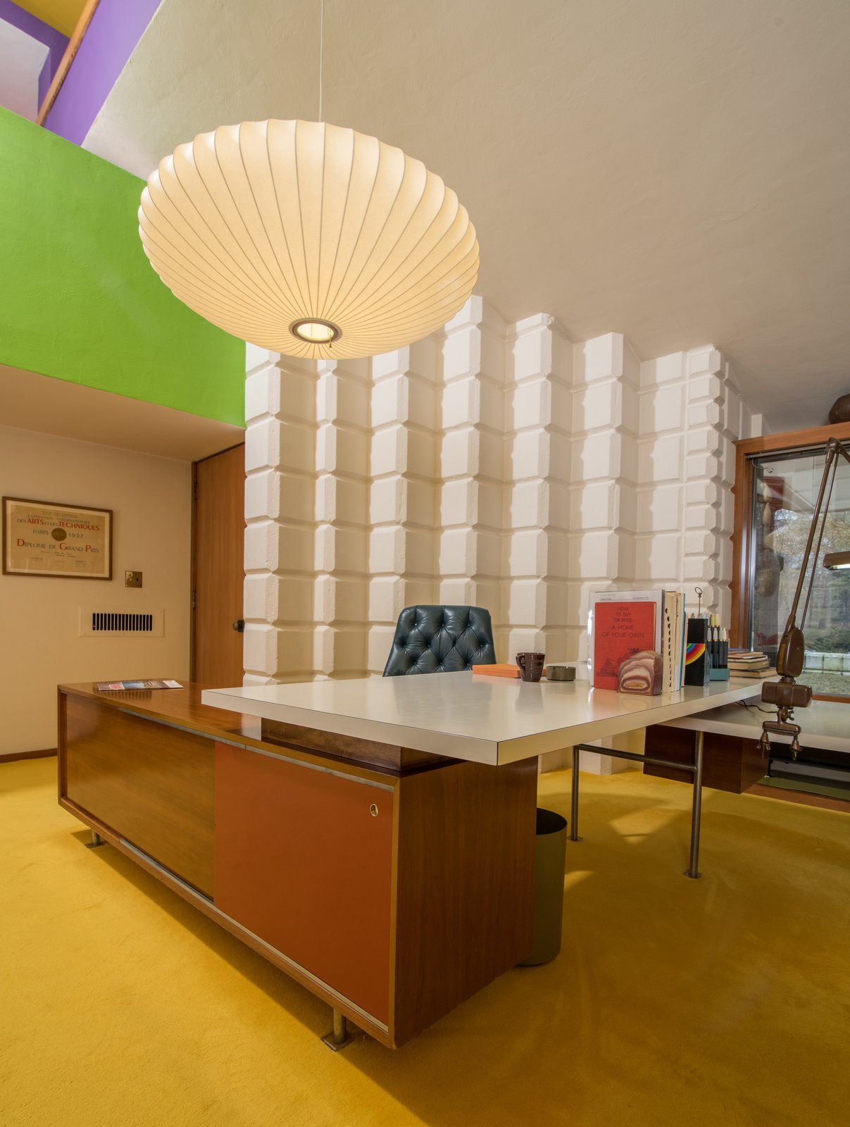 Office, Carpet Floor, Chair, and Desk Dow also incorporated iconic pieces of furniture and decorative objects into his office, like George Nelson's Saucer Lamp, which hangs above his desk.  Photo 15 of 15 in A Midcentury Time Capsule Captures an Architect's Love For Iconic Design