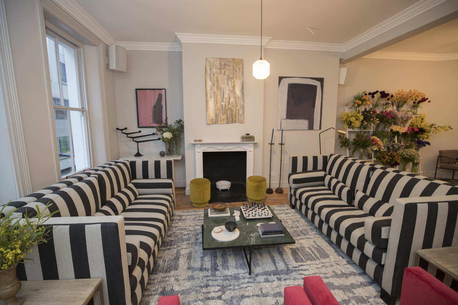Living Room, Pendant Lighting, Sofa, Standard Layout Fireplace, Rug Floor, Medium Hardwood Floor, and Coffee Tables Contemporary artwork throughout the space is curated by Beth Greenacre—the curator behind David Bowie's art collection.    Photo 6 of 17 in 6 Co-Working Clubs Catered to Women That Radiate Good Vibes and Beautiful Designs