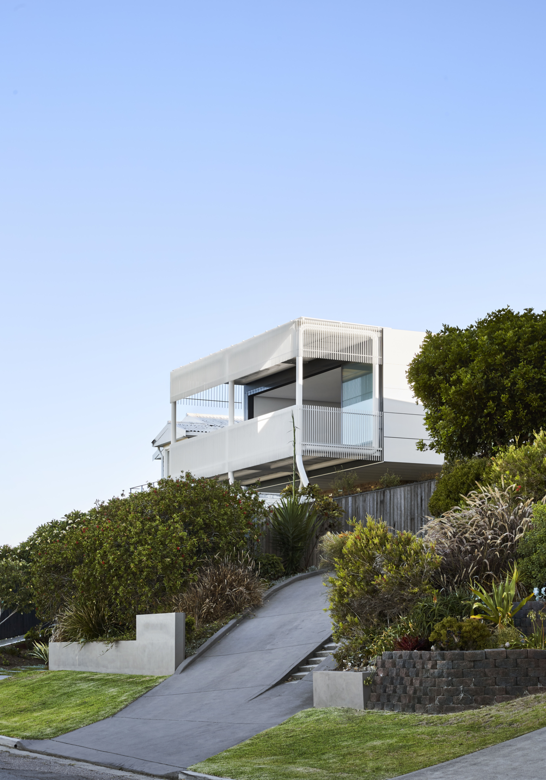 Exterior, Metal Siding Material, Flat RoofLine, House Building Type, Brick Siding Material, and Glass Siding Material Lush landscaping softens the steep driveway that leads to the garage at the base of the house.  Photos from A Futuristic Abode in Australia Draws Inspiration From Star Wars