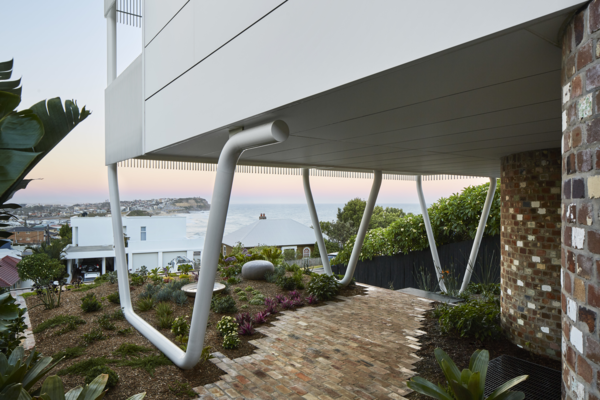 The top floor of the home is propped on three large steel supports that resembles paperclips.