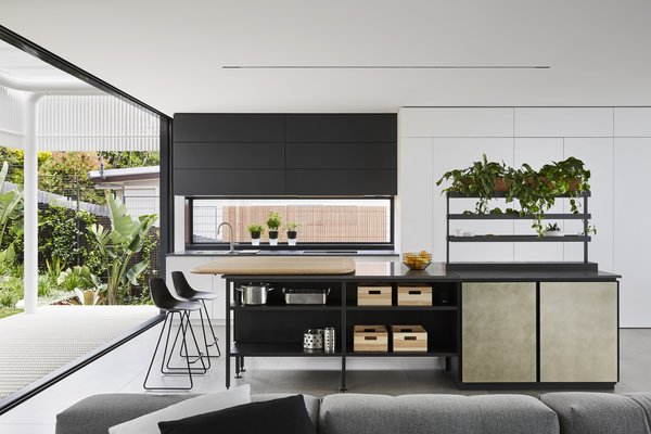 In the bright and airy kitchen, top-of-the-line appliances include a Miele integrated refrigerator, a Liebherr freezer unit, and a concealed Qasair Condari Westmore rangehood. The Salinas System Kitchen island was designed by Patricia Urquiola for Boffi.
