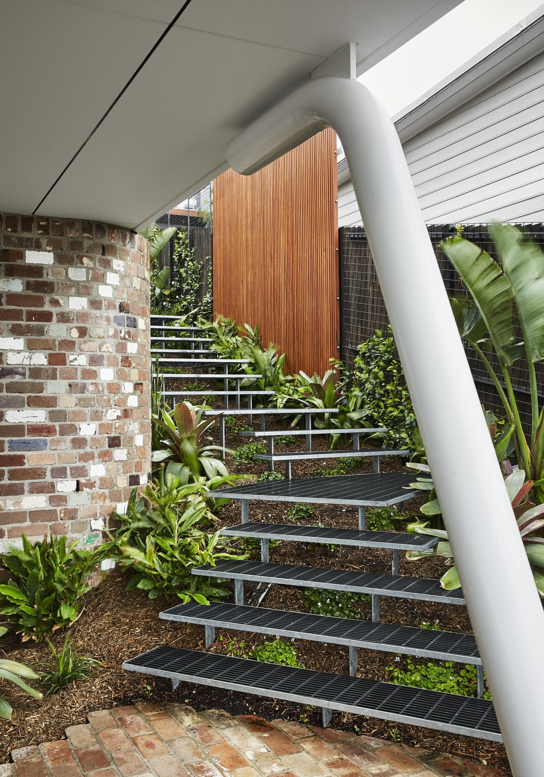 Staircase and Metal Tread The architects were able to work with the property's steep topography by creating three distinct levels for the home.  Best Photos from A Futuristic Abode in Australia Draws Inspiration From Star Wars